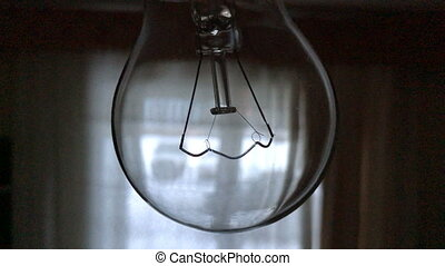 Light bulb with filament close-up in a dark room