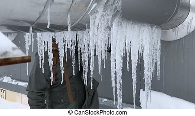 Knocking down icicles in slow motion. Icicles on a large...