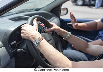 Senior learning to drive a car with a driving instructor -...