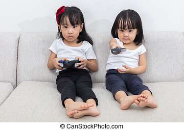 Asian Chinese little sisters playing TV games on the sofa in...