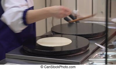 Close-up of cook frying crepe or pancake - Process of...
