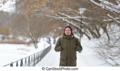 Portrait of a happy mother and son standing on the winter alley and smiles