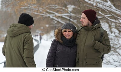 Portrait of a happy family standing on the winter alley and smiles