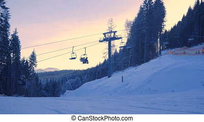 Timelapse of Ski chair-lift with skiers in snow-capped...