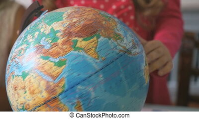 Preschool girl rotates the model of globe of world