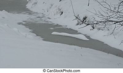 Snowing on Frosty Creek - Snowfall on a frosted creek in the...