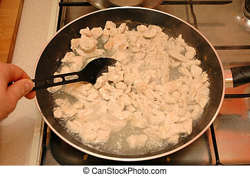 Frying the meat - frying slices of the chicken breast at the...