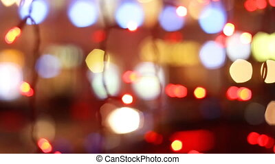 Colorful holiday bokeh night city. Blurred silhouettes of cars and people moving
