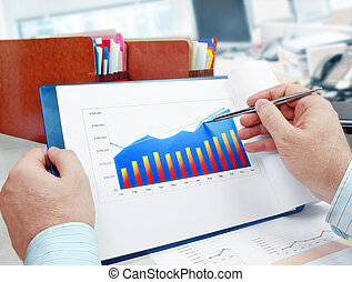 Analyzing Investment Charts - Male hand with pen on the...