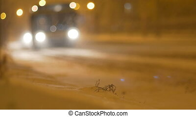 Night Snowing Traffic - Car headlights passing the avenue at...
