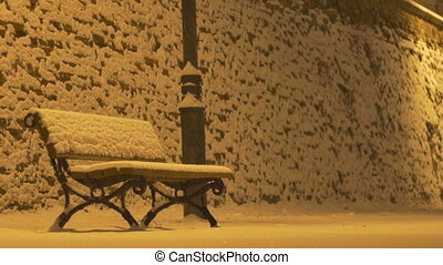 Snowing Night Bench - A bench covered in snow during a night...