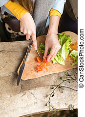 the girl cuts cherry tomatoes.