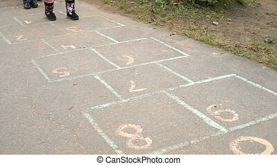 Child playing the hopscotch outdoors. Close-up