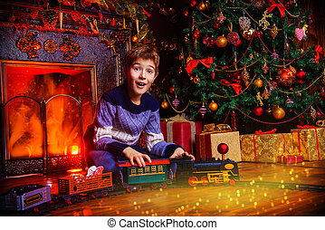 surprised boy - Cute boy playing with a toy railway near the...