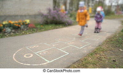 Children playing hopscotch on the asphalt
