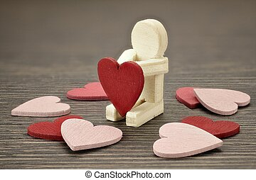 Wooden man with many red and pink hearts