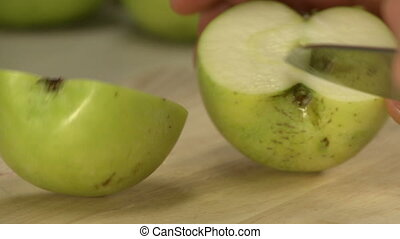 Cook cutting apple at wooden plank in kitchen - Cook cutting...