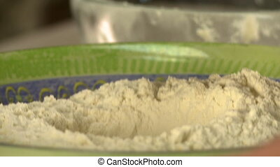 Man mixing ingredients for dough: sugar with flour