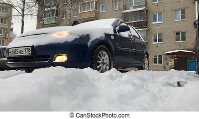 Cleaning the car from the snow. A man cleans his car from...