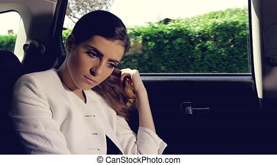 Beautiful woman in car thinking touching long hair -...