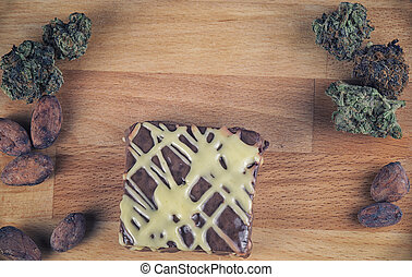 Pot brownie detail over wood with cannabis buds - Chocolate...