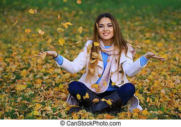 Woman Throwing Autumn Leaves Into The Air
