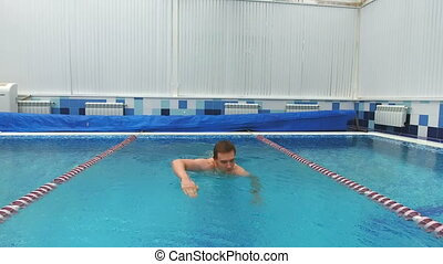 Young man swimming the front crawl in a pool. Professional...