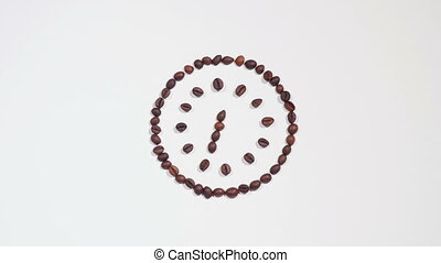 Time for coffee - Clock made of coffee beans on white...