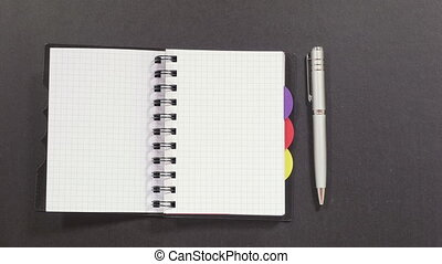 Turning over pages of notebook - Black dotty spiral notebook...