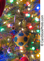 Holiday season, christmas tree decorations glow under...