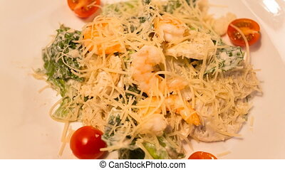 Caesar salad with shrimp on a plate closeup