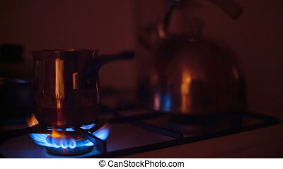 Little saucepan is heated on a gas burner at night