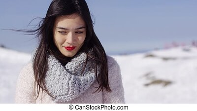 Pretty young woman in sweater on ski slope - Thoughtful...