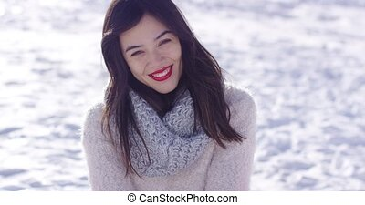 Smiling young woman sat on snow - Smiling young woman in...