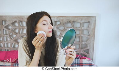 Young beautiful woman doing make up and smile into camera