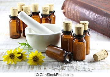 homeopathic arnica pills in brown bottles on wooden...