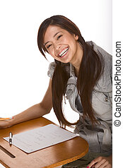 Friendly excited Asian college student by desk - Ethnic...