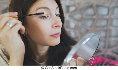 Beautiful woman holding a mirror and drawing eyebrows on face - make up concepts