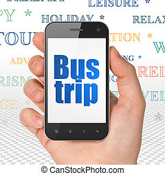 Tourism concept: Hand Holding Smartphone with Bus Trip on...