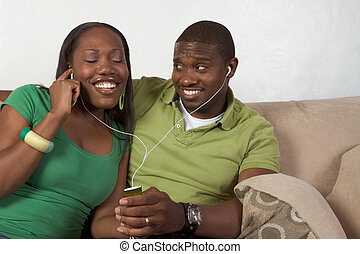 Happy young ethnic black couple listening music - Young...