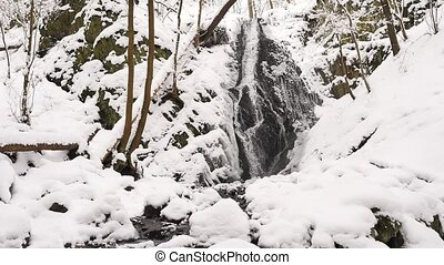 Snowy waterfall in winter forest. Basalt stones bellow...