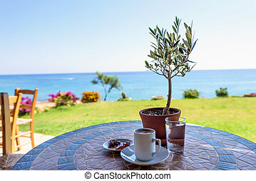 Cup of coffee on a table with olive tree - Traditional cup...