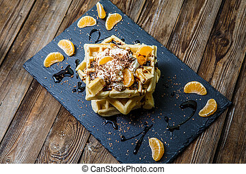 Photo of several Belgian waffles with chocolate, tangerines...