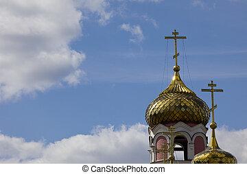 Church dome with cross on sunny sky