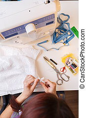 Seamstress with cloth in hand in studio with sewing machine