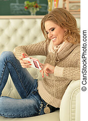 young woman using phone, sitting on sofa