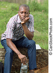 Young man sitting on a tree trunk.