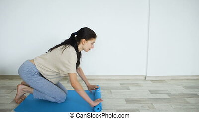 Young woman doing yoga exercise - opening her yoga mat