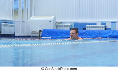 Young man actively swimming in a swimming pool. You can use...