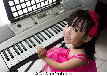 Happy Asian Chinese little girl playing electric piano...